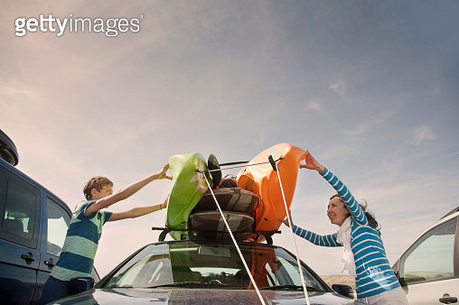 Mother and son stacking kayaks on top of car - gettyimageskorea