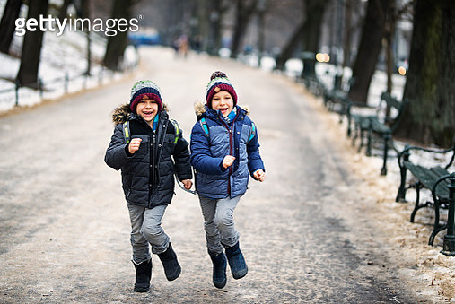 Happy little boys running from school in winter - gettyimageskorea