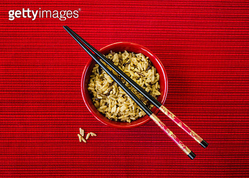 Bowl of rice and chopsticks on red background - gettyimageskorea