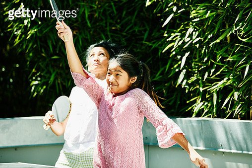 Young girl playing table tennis in backyard with aunt on sunny afternoon - gettyimageskorea