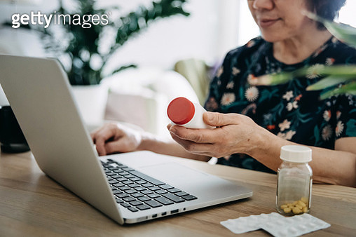 Senior Asian woman video conferencing with laptop to connect with her family doctor, consulting about medicine during self isolation at home in Covid-19 health crisis - gettyimageskorea