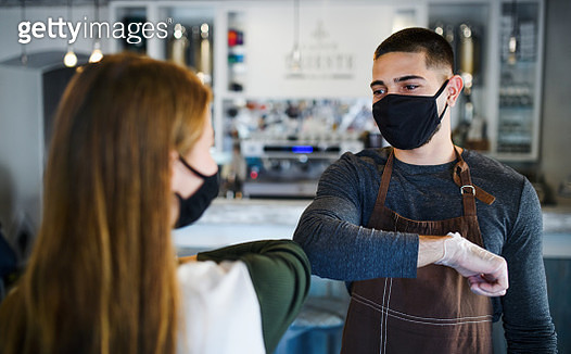 Portrait of young waiter and waitress with face mask standing in coffee shop, elbow bumping. - gettyimageskorea