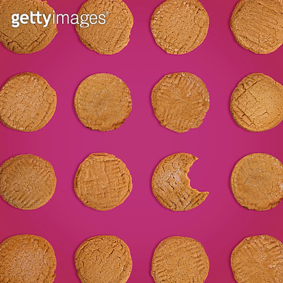 Homemade peanut butter cookies  - one with a bite mark - arranged in a grid on a magenta background. - gettyimageskorea