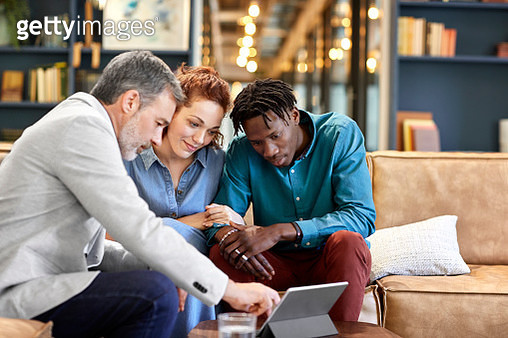 Multi-ethnic customer and mature salesman looking at digital tablet. Financial advisor is planning investment with young couple during meeting. They are at creative workplace. - gettyimageskorea