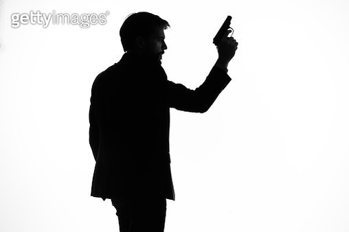 Silhouette of a man with a gun in his hands - gettyimageskorea