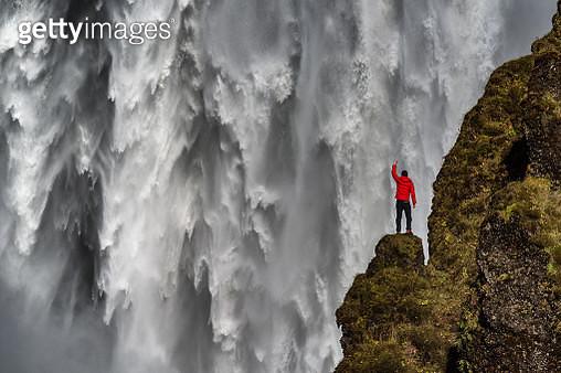 A man standing below Skogafoss waterfall - gettyimageskorea