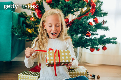 Cute little blond girl sitting on the floor near the christmas tree and opening a christmas gift. - gettyimageskorea