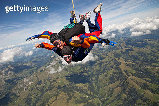 Tandem skydivers plunge through lofty skies above mountains - gettyimageskorea