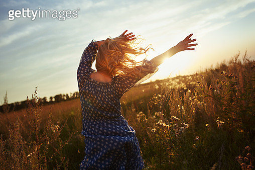Woman with wavy hair dancing in the meadow during sunset - gettyimageskorea