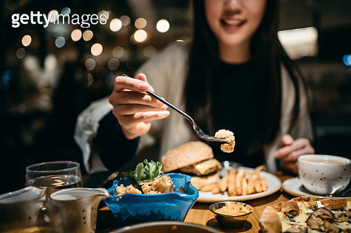 Smiling young woman enjoying her meal and sharing her food in a restaurant - gettyimageskorea