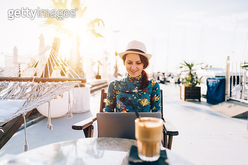 Happy tourist woman on beach holiday sitting at cafe and using laptop - gettyimageskorea