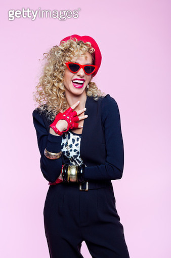 Fashion portrait of beautiful blond curly hair woman wearing leopard print top, black pants and jacket, red beret, gloves and sunglasses. Excited female in 80's style outfit. Studio shot on pink background. - gettyimageskorea