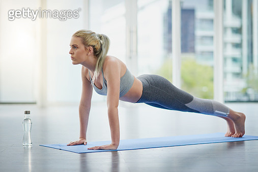Shot of a sporty young woman exercising in a studio - gettyimageskorea