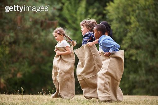Friends Having Sack Race At Public Park - gettyimageskorea