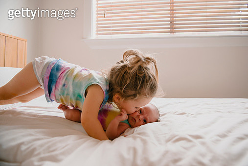 girl wearing tie dye kissing baby - gettyimageskorea