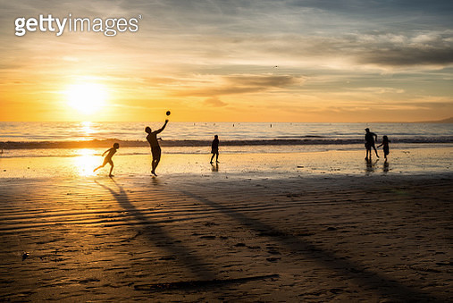 Silhopuettes of a family with kids playing footbal in sunset light on Santa Monica beach. - gettyimageskorea