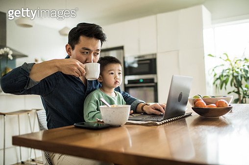 Father multi-tasking with young son (2 yrs) at kitchen table - gettyimageskorea