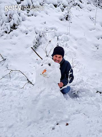 Man Making Snowman During Winter - gettyimageskorea