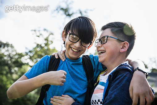 School age brothers laughing outdoors - gettyimageskorea