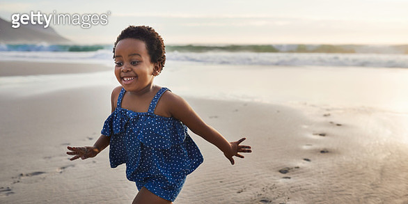 Shot of an adorable little girl having fun on the beach at sunset - gettyimageskorea