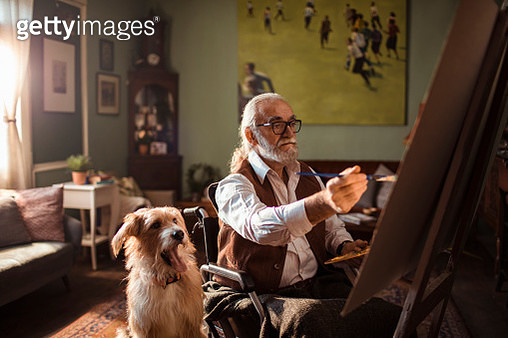 Close up of a senior man painting while sitting in a wheelchair with his dog on the side - gettyimageskorea
