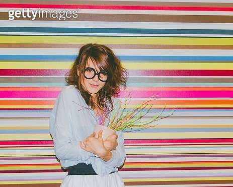 Portrait Of Beautiful Woman Holding Artificial Potted Plant Against Multi Colored Wall - gettyimageskorea