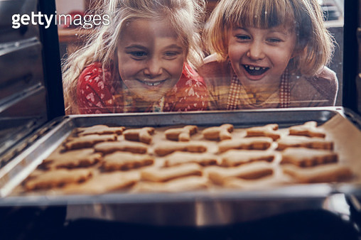 Little Girls Waiting for Christmas Cookies to Bake in the Oven - gettyimageskorea