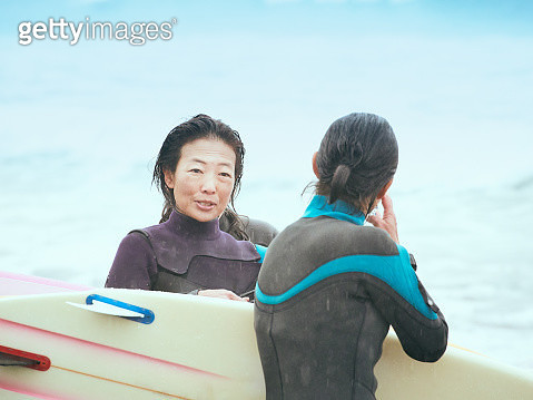 Women are having fun at a beach with a surfboard - gettyimageskorea