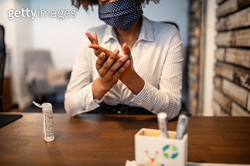 Businesswoman sitting at her desk cleaning hands with sanitizer - gettyimageskorea