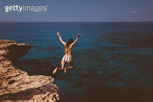 Young active woman jumping off cliff and falling into ocean on tropical island summer holidays - gettyimageskorea