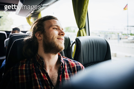 A young man leans back to enjoy the view whilst taking a bus trip. - gettyimageskorea