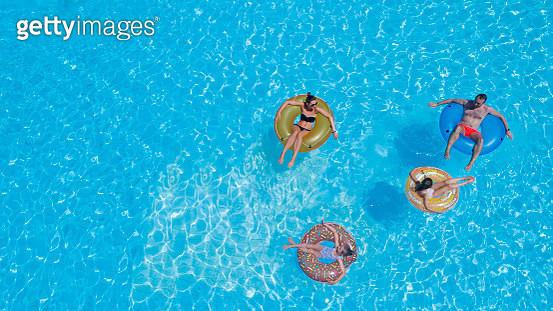 family in inflatable rings in pool - gettyimageskorea