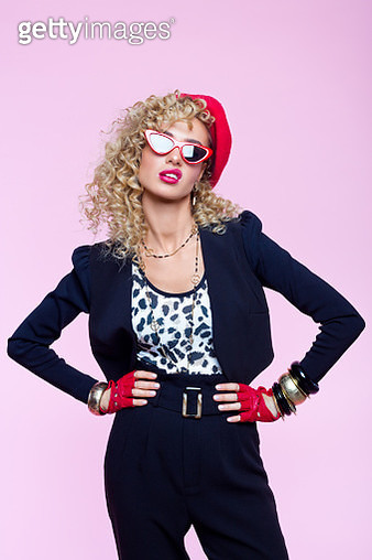Beautiful blond curly hair woman wearing leopard print top, black pants and jacket, red beret, gloves and sunglasses. Displeased female in 80's style outfit. Studio shot on pink background. - gettyimageskorea