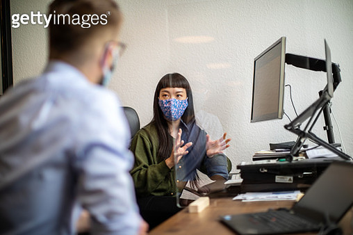 Businesswoman discussing work through glass partition with colleague - gettyimageskorea