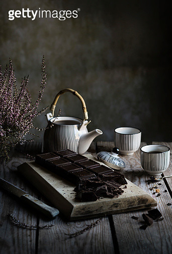 Tea time: teapot, cups of tea and dark chocolate on wooden table - gettyimageskorea