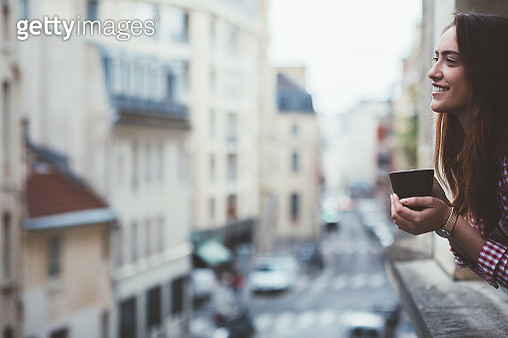 Relaxed woman drinking coffee on the window in Paris - gettyimageskorea