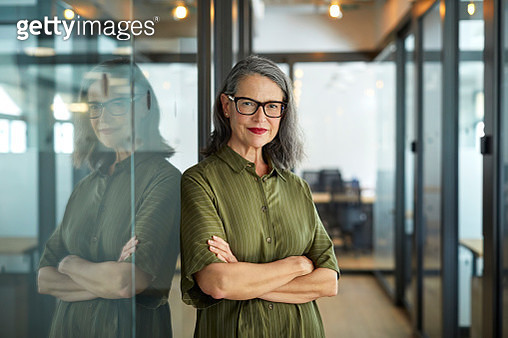 Portrait of mature businesswoman leaning on glass wall in corridor. Confident female entrepreneur is standing with arms crossed. She is wearing smart casuals at office. - gettyimageskorea