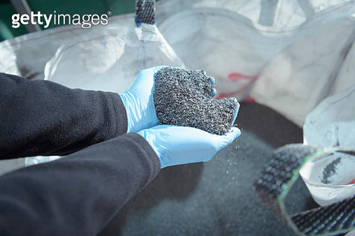 Worker holding recycled metals from catalytic converters in recycling factory - gettyimageskorea