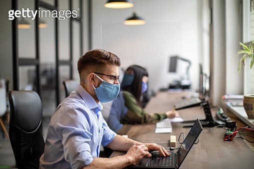 Business people maintaining social distance while working in office - gettyimageskorea