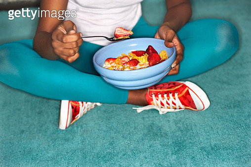 Woman Sitting on Floor Eating Cereal with Strawberries - gettyimageskorea