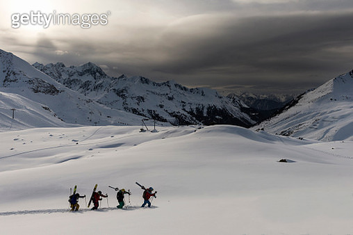 A group of skiers hiking up a mountain - gettyimageskorea