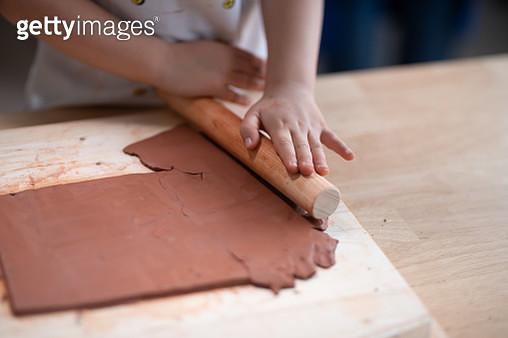 Girl rolling clay in classroom - gettyimageskorea