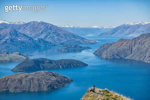 an asian chinese female sitting on the peak of the hill with lake wanaka background during day time - gettyimageskorea