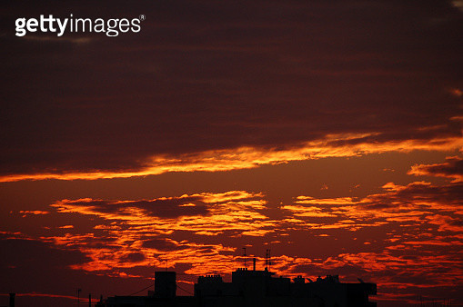 Rooftop silhouettes under a burning sky - gettyimageskorea