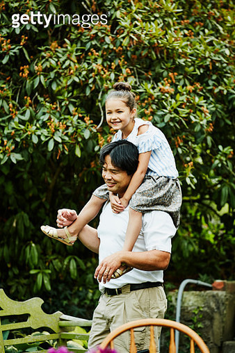 Smiling young girl riding on uncles shoulders in backyard garden - gettyimageskorea