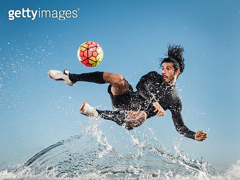 Water spraying on Hispanic man kicking soccer ball - gettyimageskorea