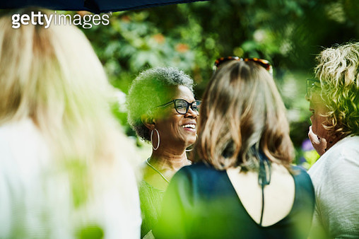 Smiling friends in discussion during backyard garden party - gettyimageskorea