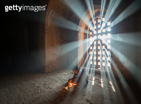 A boy with a candle by a window. - gettyimageskorea