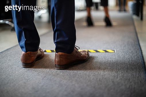 Man in queue at office for safe entry checks - gettyimageskorea