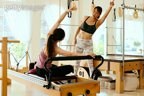 Senior woman pilates instructor leading class on pilates reformers in fitness studio - gettyimageskorea